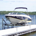 Speed boat on cantilever lift next to aluminium docking system