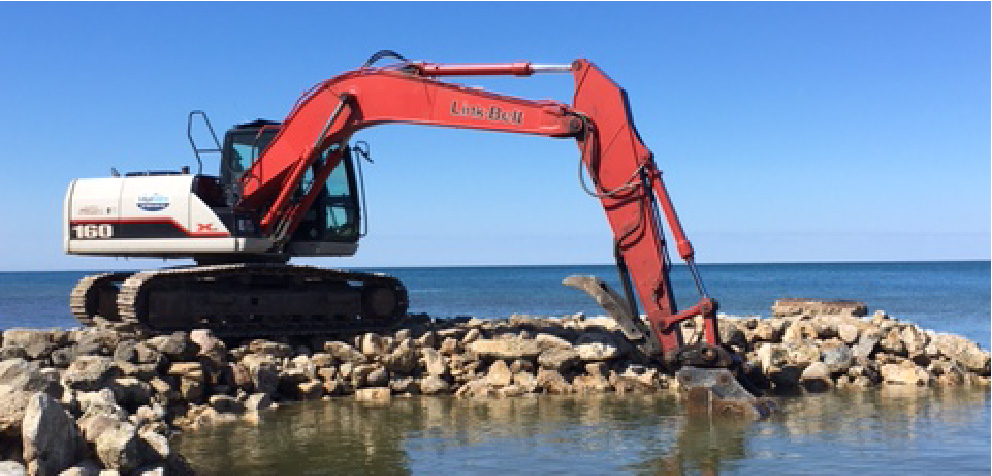 Excavator on harbour lifting rocks
