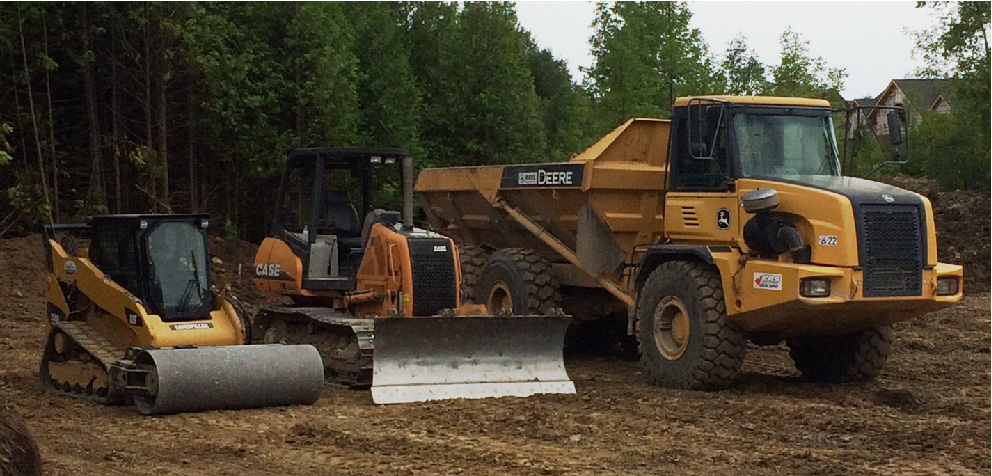 Skidsteer, excavator and dump truck parked on site
