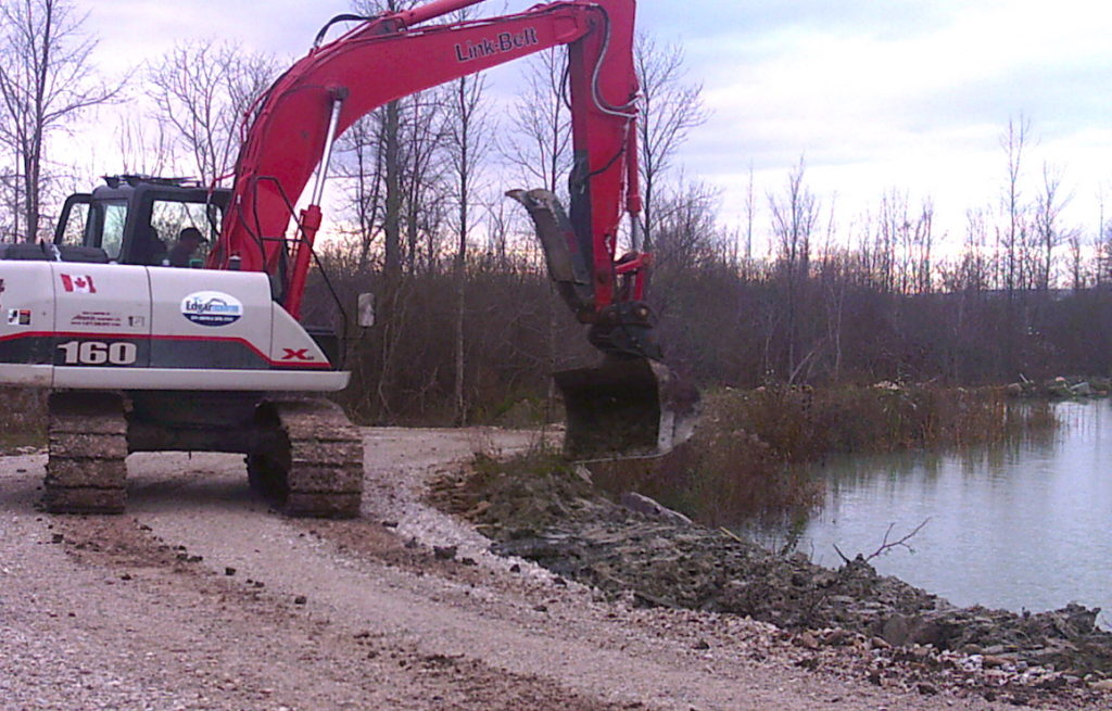 Large excavator next to pond