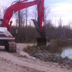 Large excavator next to pond